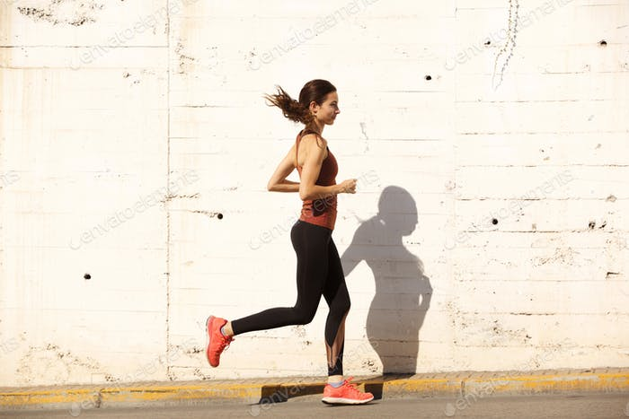 Side portrait of fit young woman running outdoors