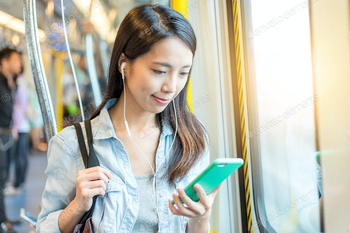 Woman listen to music on phone on train