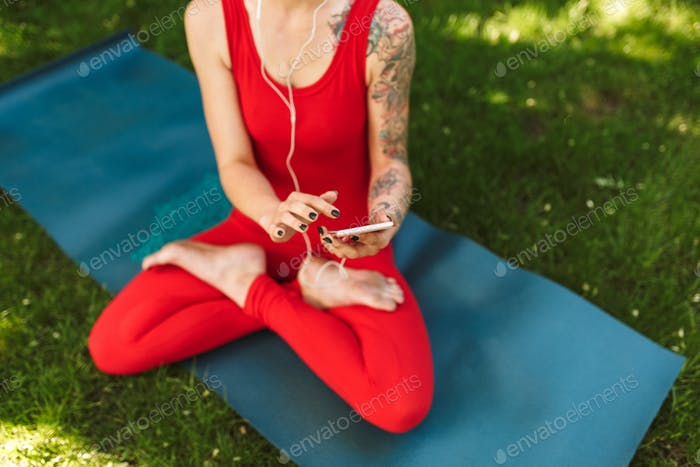 Thumbnail for Photo of woman body in red jumpsuit sitting in lotus pose on yoga mat and using cellphone in park