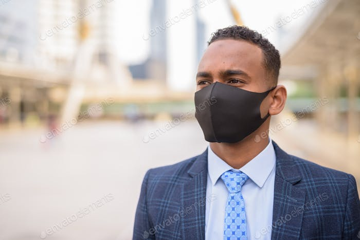Face of young African businessman with mask for protection from corona virus outbreak thinking in