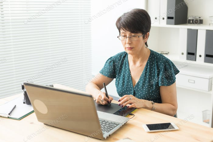 Business, technology and people concept - happy woman using graphics tablet