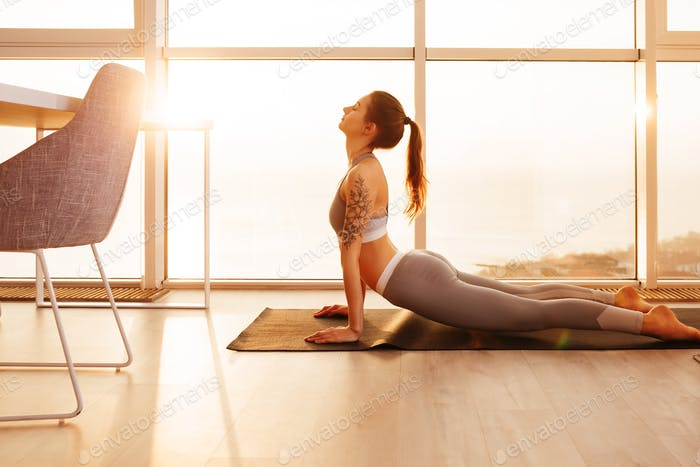 Nice girl in sporty top and leggings practicing yoga on yoga mat at home over beautiful window view