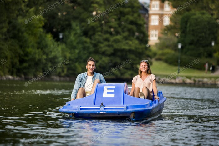 Happy friends pedal boating on river in city