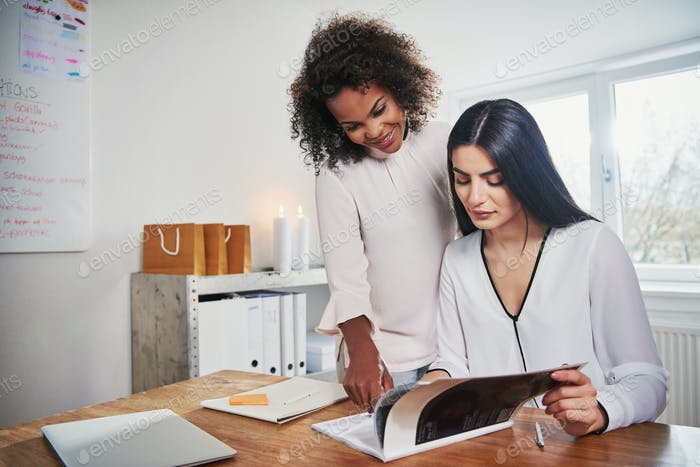 Two women working with documents at workplace