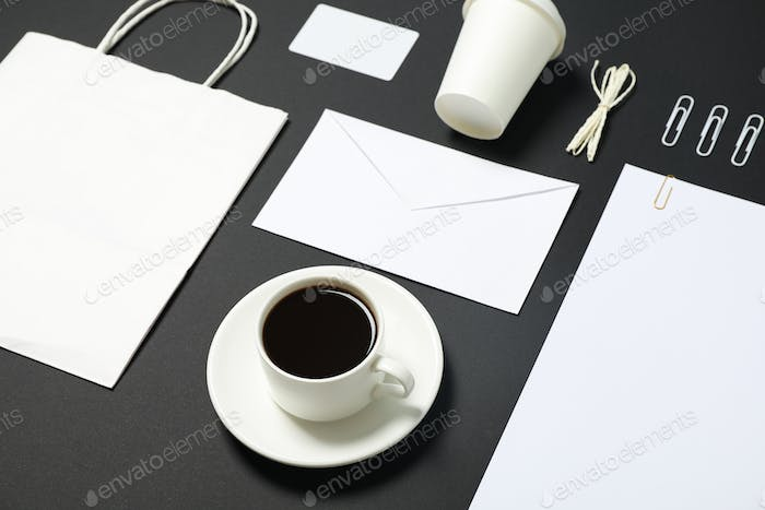 Blank stationery, paper bag and cup of coffee on black background. Mockup
