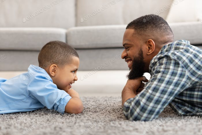 African Daddy And Son Looking At One Another At Home