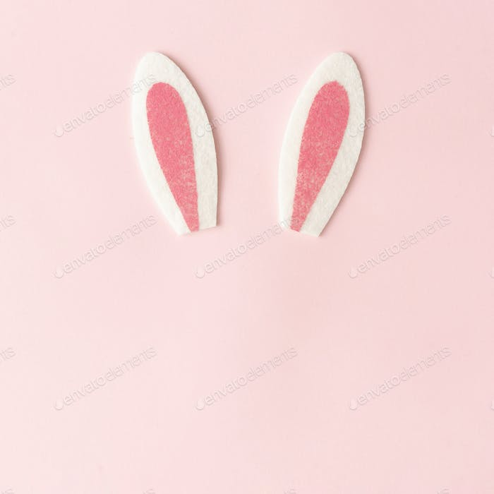 Bunny rabbit ears on pastel pink background. Happy Easter minimal concept. Flat lay.
