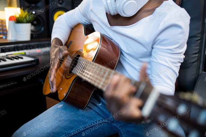Acoustic guitar held by musician of African ethnicity during process of singing