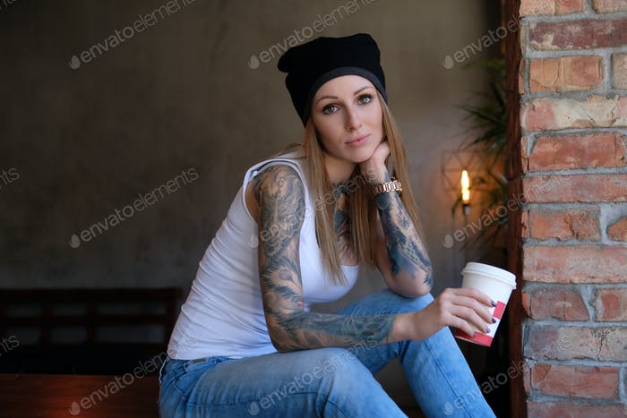 Portrait of a tattooed blonde hipster girl in a room with loft interior