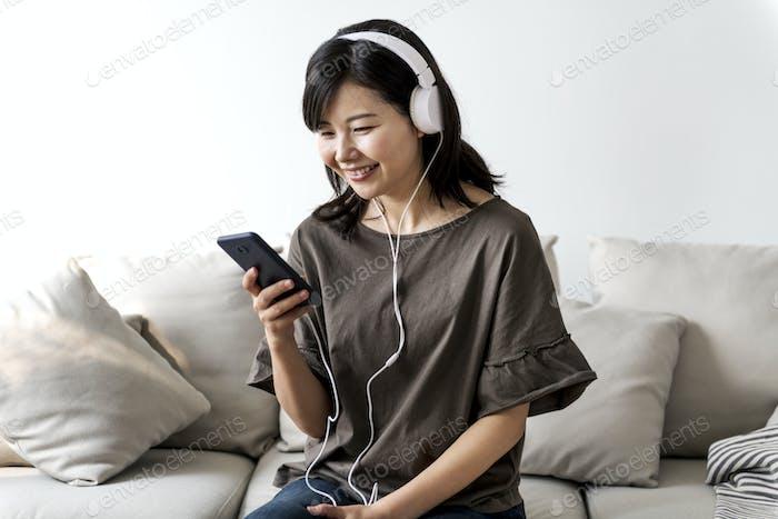 Asiatische Frau genießen Musik zu Hause