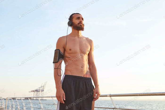 Young attractive sporty bearded man after extreme sport at the seaside, rest after jogging