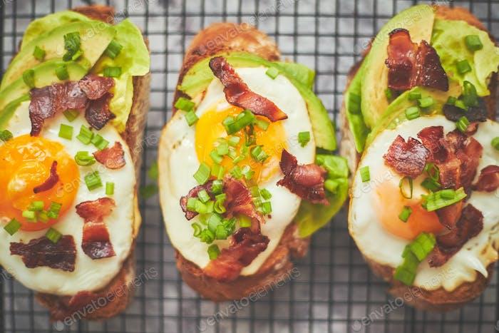 Frühstückskonzept. Leckere leckere hausgemachte Toasts mit Spiegelei, Speck, Avocado, Salat und Schnittlauch