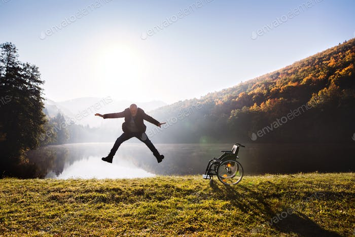Senior man jumping by the wheelchair in autumn nature.