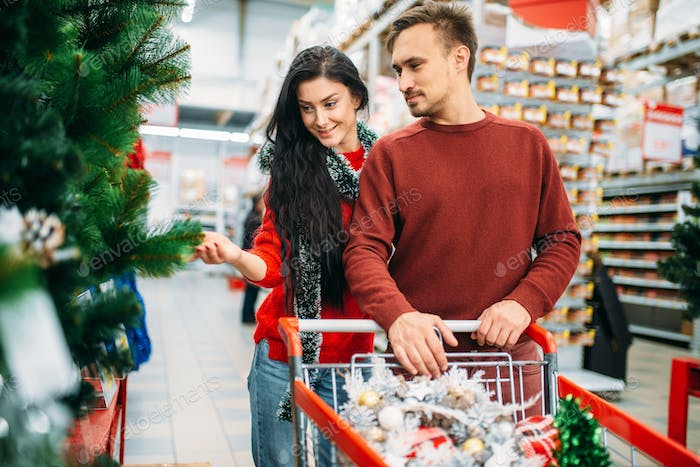 Couple buying christmas tree in supermarket