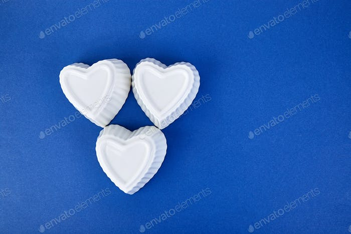 White ceramic hearts on blue trend color background. Flat lay composition.
