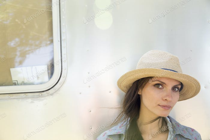 A young woman wearing a hat sitting in the shade of a silver coloured trailer.