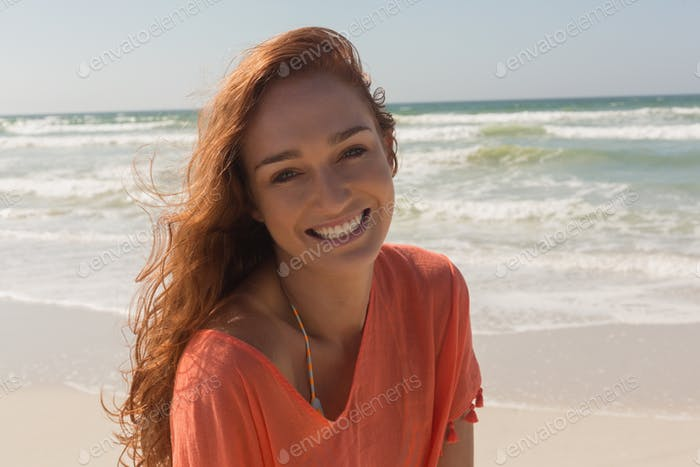 Front view of beautiful happy young Caucasian woman looking at camera on the beach. She is smiling