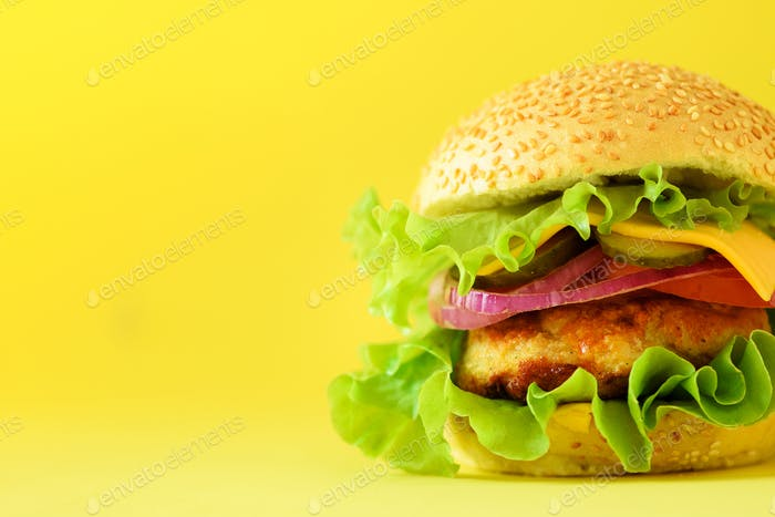Macro view of tasty burger with beef, cheese, lettuce, onion, tomatoes on yellow background. Close
