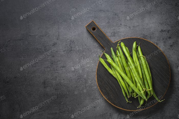 Green beans on black slate background