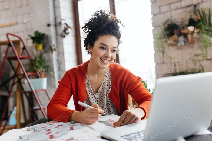 Young smilng woman with dark curly hair sitting at the table hap