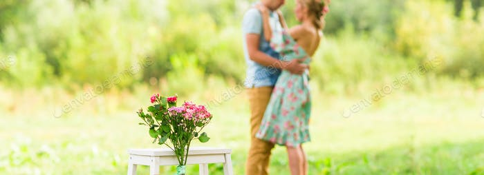 Happy Romantic couple hugging. Focus on flowers. selective focuse