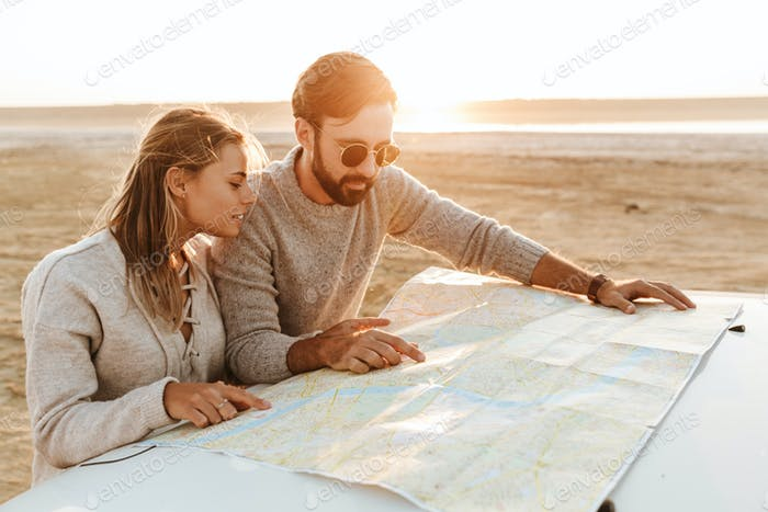 Attractive young couple looking at the travel map