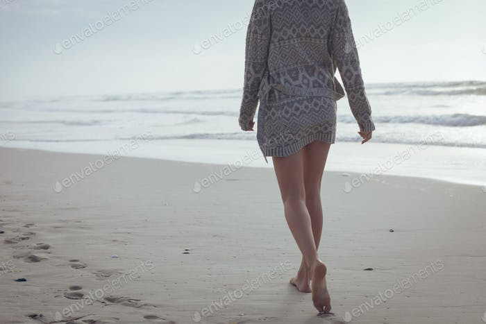 Low section of young Caucasian woman walking on the sand at beach