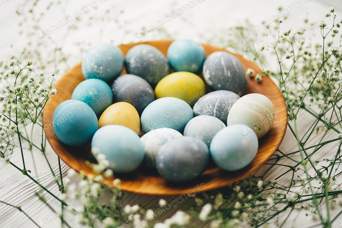 Stylish easter eggs in wooden plate on white wooden background
