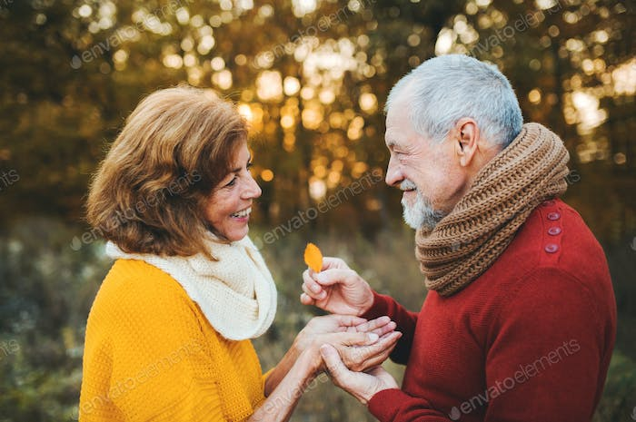 A senior couple standing in an autumn nature at sunset, looking at each other.