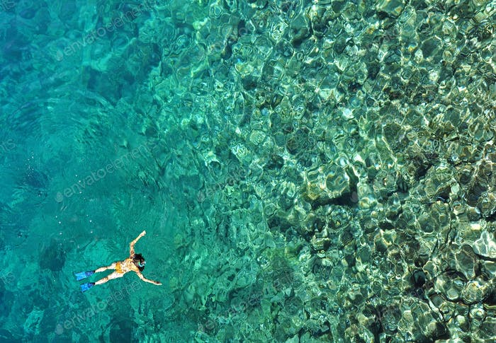 Aerial view of woman snorkeling in tropical sea water. Drone view