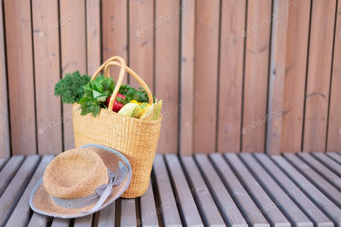 Straw basket with organic vegetables and woman hat over wooden background. Healthy food, vegetarian
