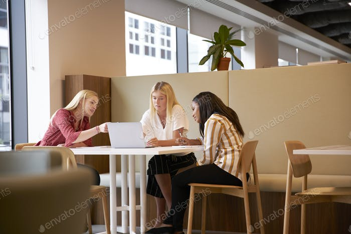 Group Of Young Businesswomen Sitting Around Table And Collaborating