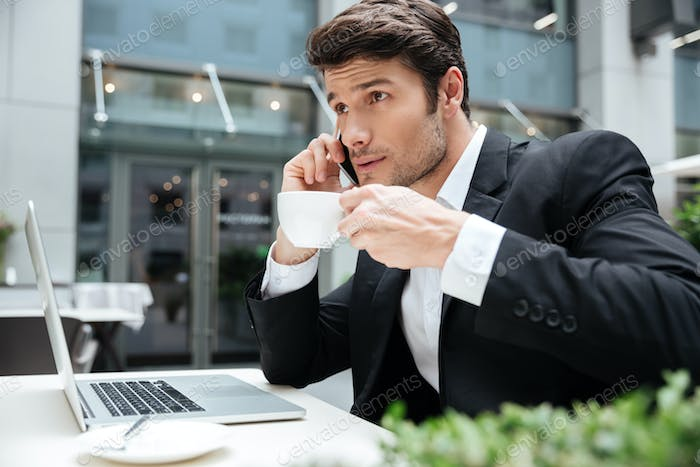 Businessman talking on cell phone and drinking coffee in cafe