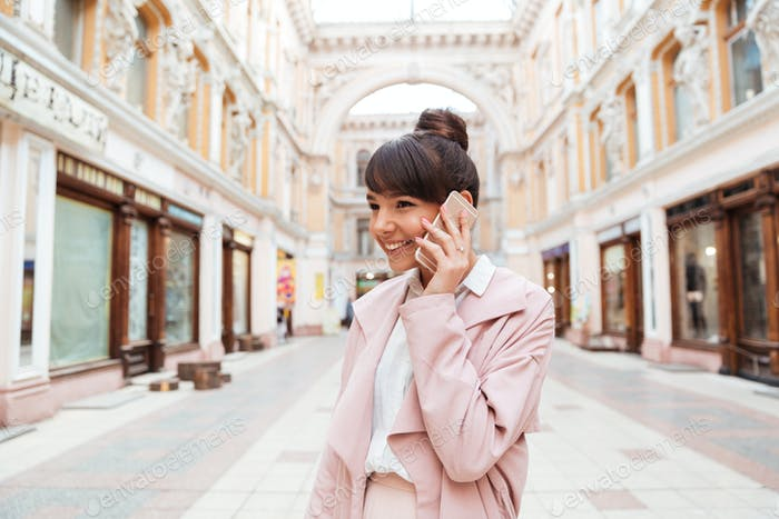 Girl talking on mobile phone while standing at the street