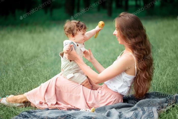 Junge schöne Mutter sitzt mit ihrem kleinen Sohn