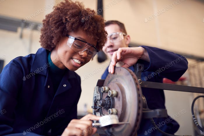 Male And Female Students Working On Car Brakes On Auto Mechanic Apprenticeship Course At College