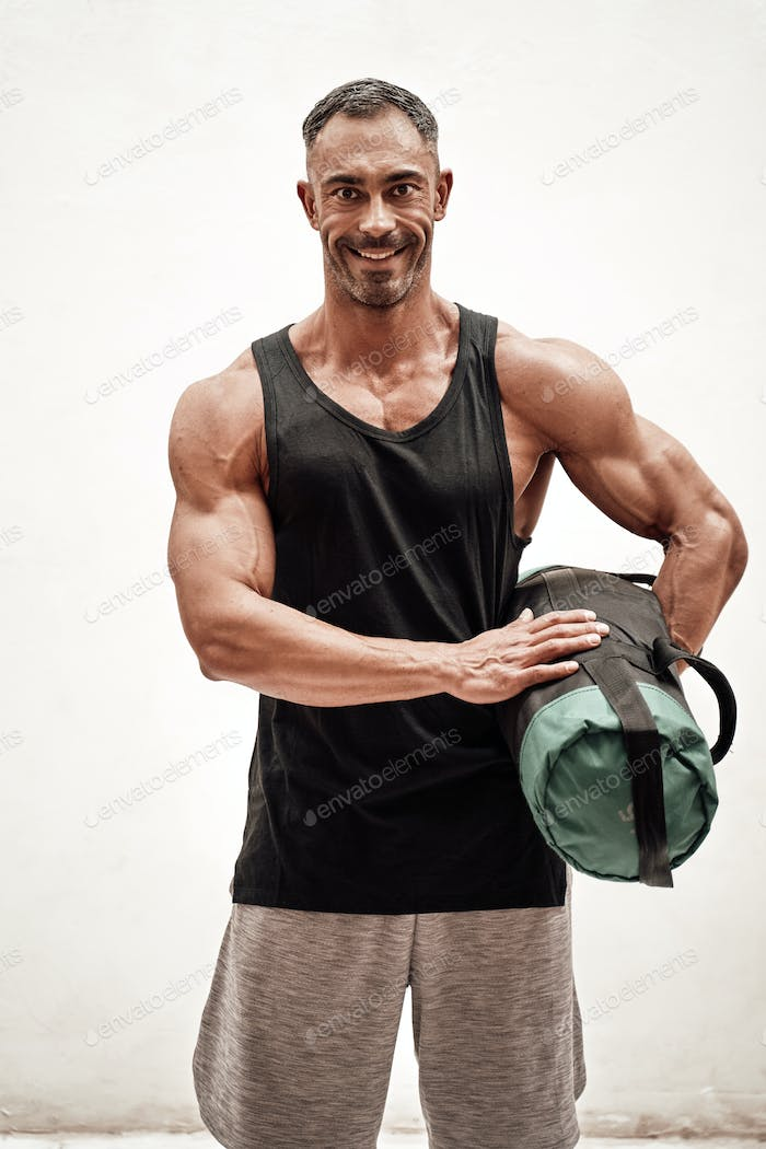 Strong and muscular athlete posing in a bright studio with a weight bag looking fresh