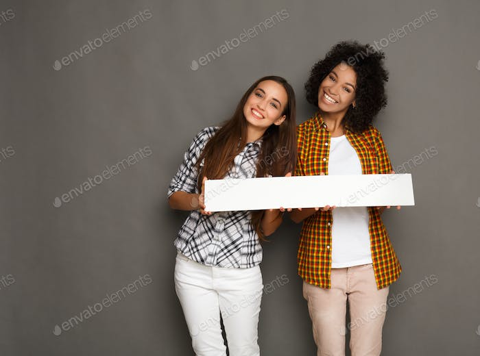 Two girlfriends holding blank white banner