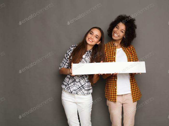 Zwei Freundinnen halten leere weiße Banner