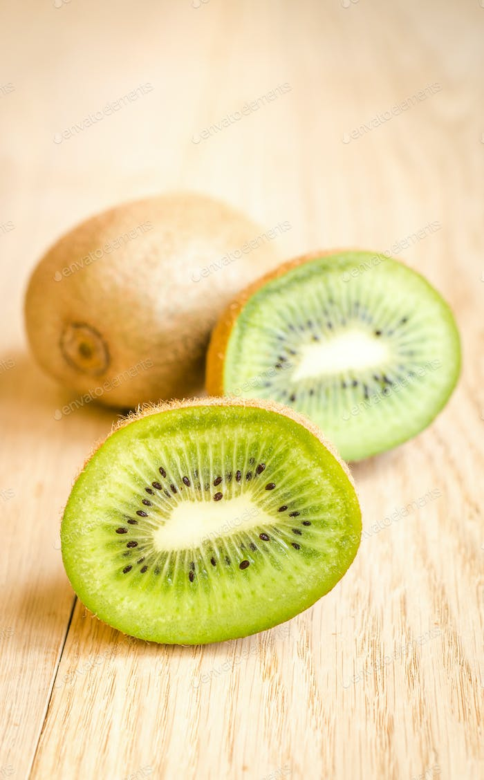Kiwi on the wooden background: whole fruit and cross section