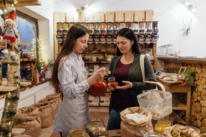 Woman buying herbs and spices in plastic free shop.