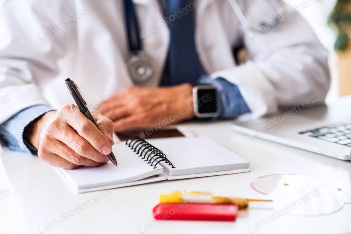 Senior doctor working at the office desk.