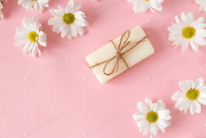 Flat lay composition with hand made soap bars and lavender flowers on violet background