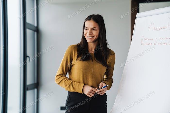 Porträt der Geschäftsfrau stehend von Flipchart während der Arbeit im Büro