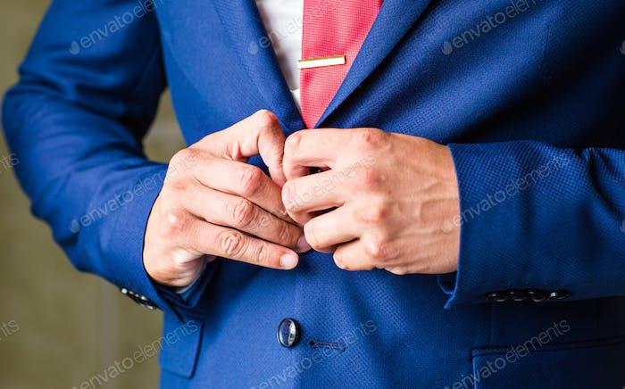 Man buttoning jacket close-up