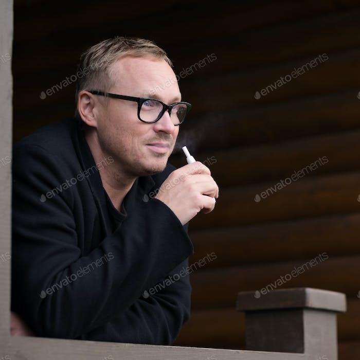 Caucasian man smoking modern hybrid cigarette device outdoor