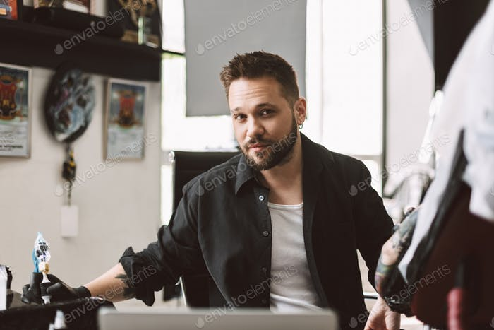 Professional tattooer dreamily looking in camera prepearing doin