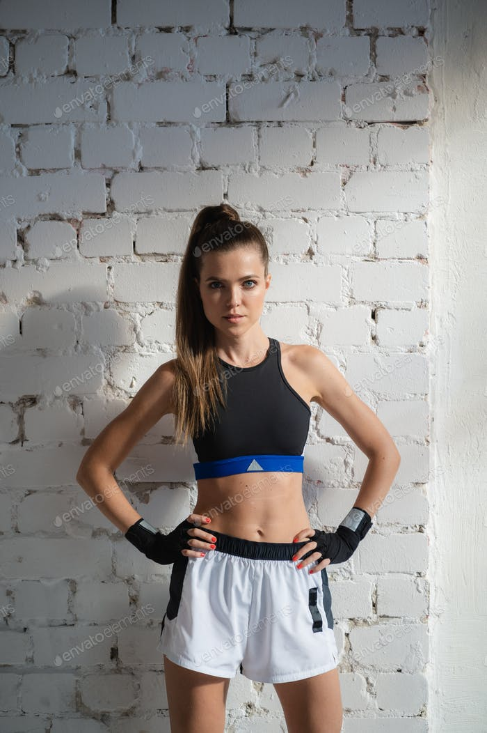 Close up of one young woman wrapping hands with black boxing wraps in gym practice boxing indoor