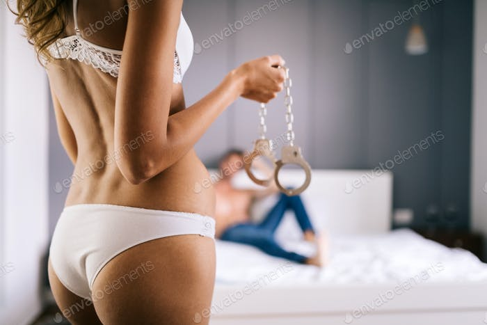 Sexy woman and man playing domination games in bed