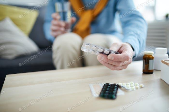Senior Man taking Pills Close up